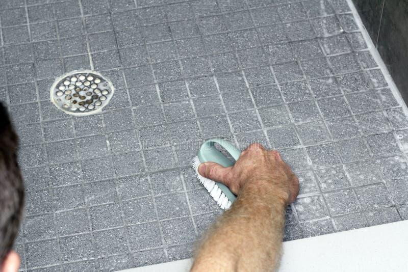Man Scrubbing a Shower Floor stock photography