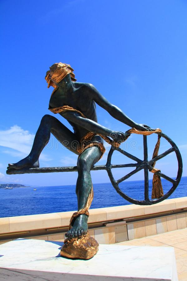 Man Sculpture in Monaco. A man sculpture in Monaco. This sculpture is on the beach. With gold ribbon on his body and one round wheel in his hand. The blue sky stock photography