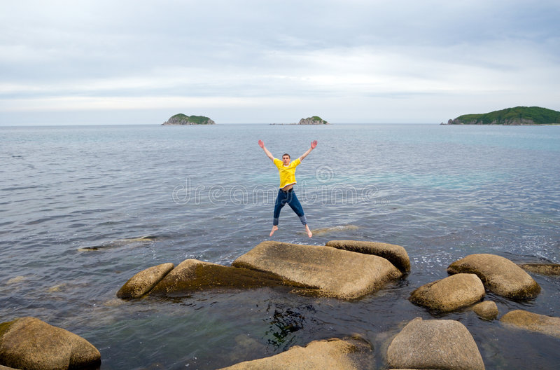 Man and sea. The young man jumps on a stone at the sea having stretched hands stock photos