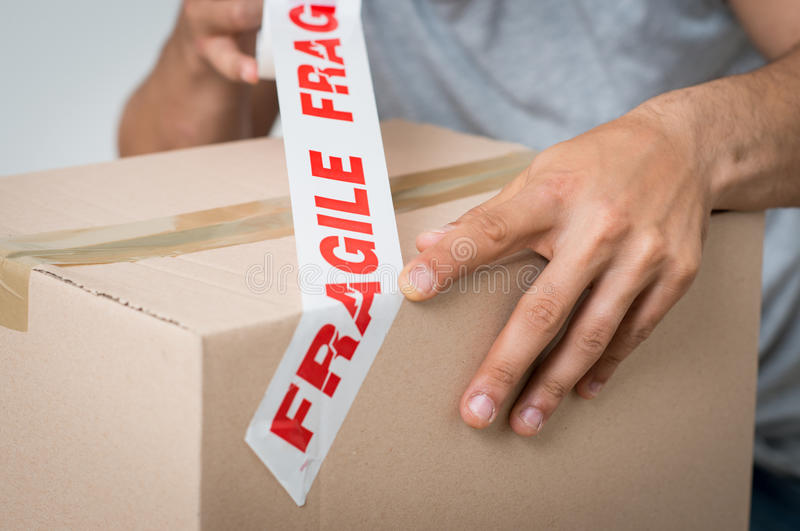 Man Sealing Box With Fragile Adhesive stock images