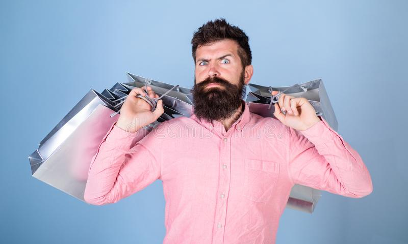 Man searching for cool items, holiday rush concept. Bearded man in pink shirt isolated on blue background. Metrosexual royalty free stock photo