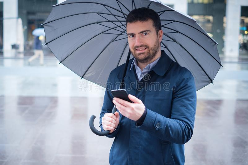 Man watching on smartphone the weather forecast on a rainy day royalty free stock photography