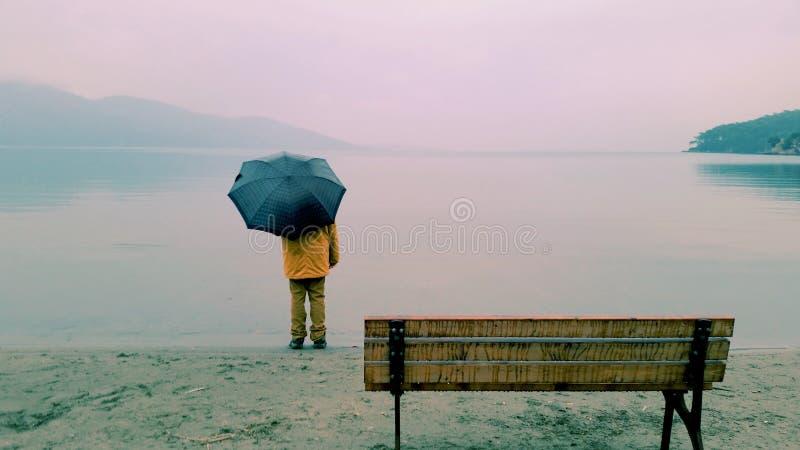 Man on seashore holding umbrella stock photography