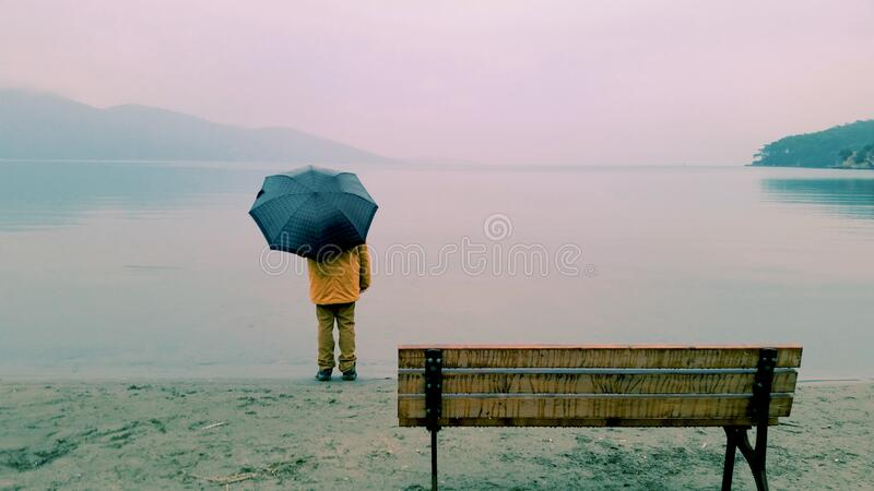 Man on seashore holding umbrella stock photography