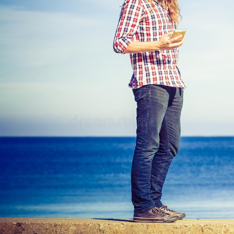 Man by seaside receiving a call on his phone stock image