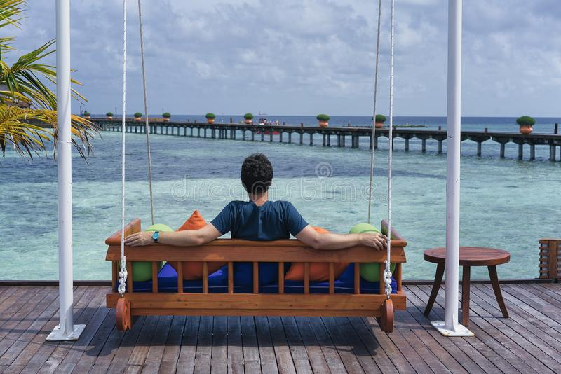 Man seated in a bench in a Maldives Islands Resort stock photos