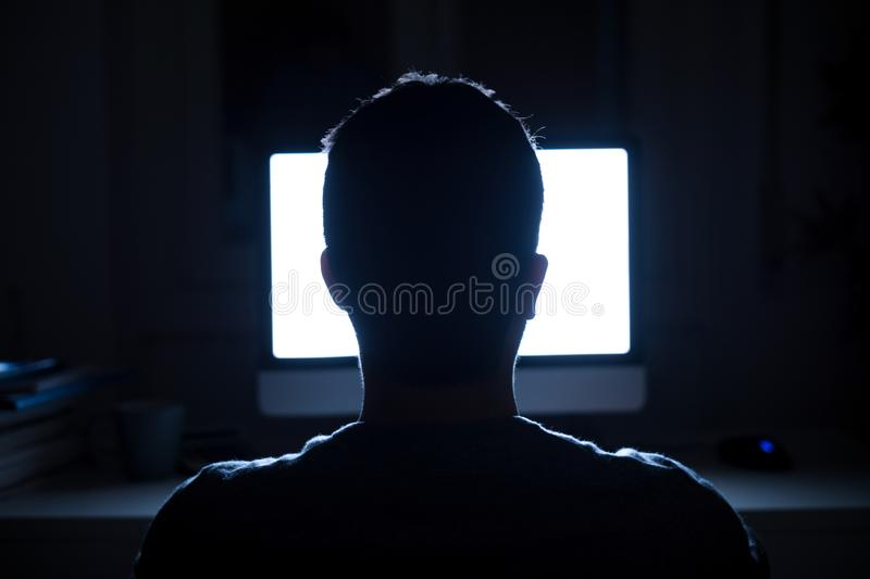 Man seated in front of computer monitor at night royalty free stock image
