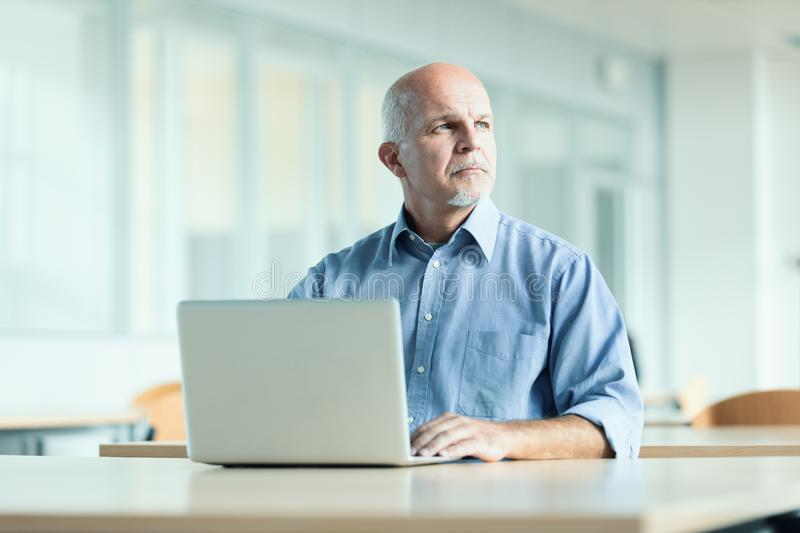 Man seated in front of laptop computer. Business man seated in front of laptop computer while looking off in the distance royalty free stock images