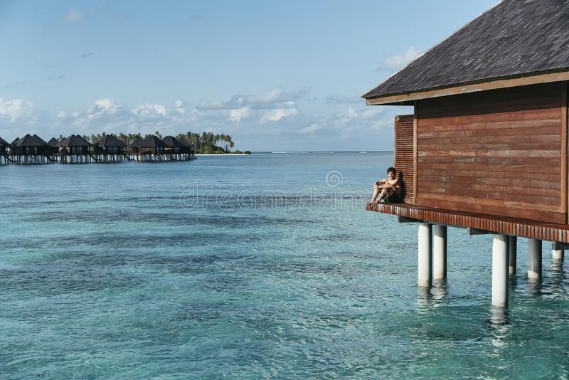 A man seated in a water villa in Maldives islands enjoying the turquoise water.  stock images