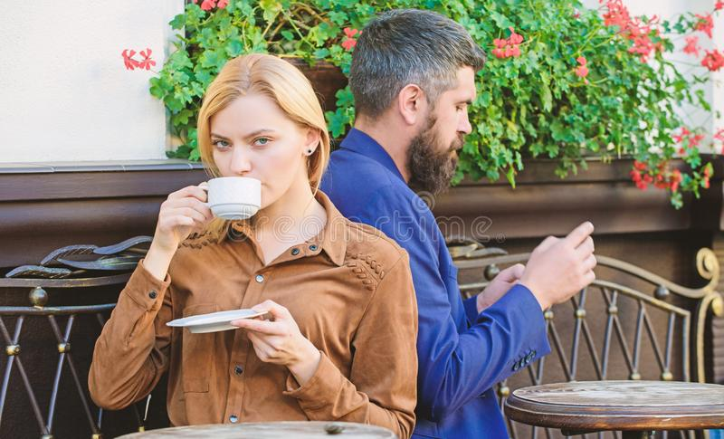 Man secret messaging cheating on wife. Cheat and betrayal. Family weekend. Married lovely couple relaxing together. Couple cafe terrace drink coffee. Couple in stock image
