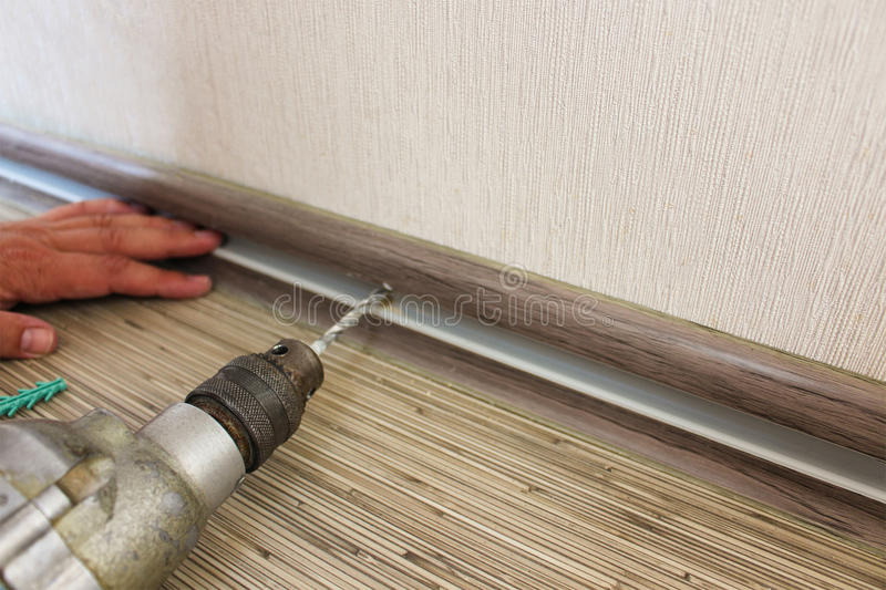 Man secures baseboard to wall. The man secures the baseboard to the wall stock photography