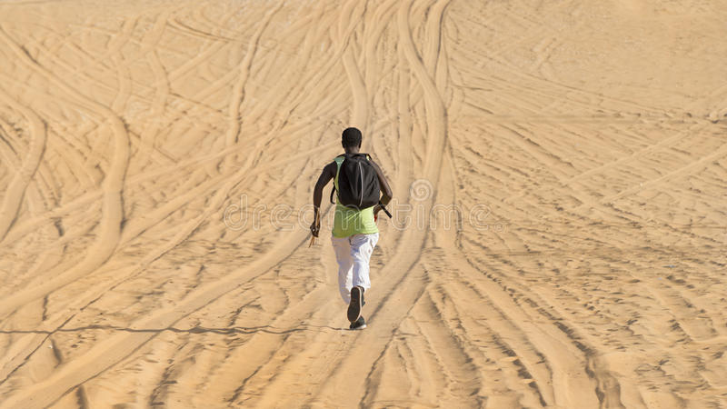 Man seen by back and running on a sand road stock image
