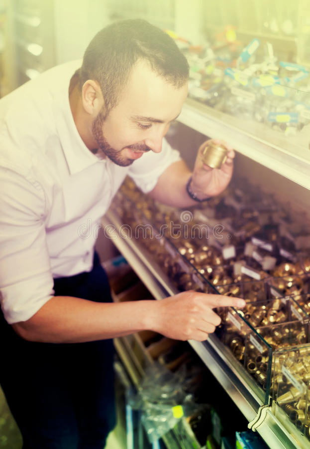 Man selecting metallic faucet. Portrait of smiling adult man selecting metallic faucet in household department royalty free stock photos