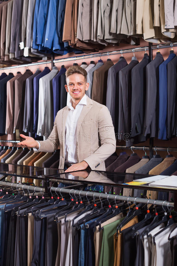 Download Man Seller Displaying Diverse Suits In Men's Cloths Store Stock Photo - Image: 83702092