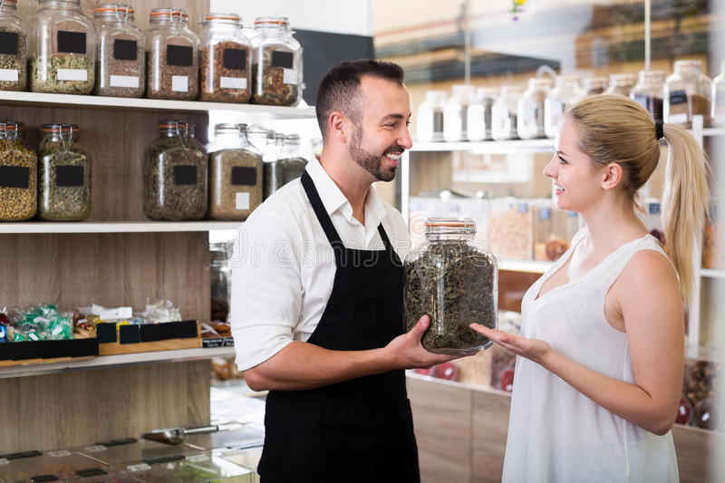 Man seller picking glass can with dried herbs. Positive men seller picking glass can with dried herbs and helping customer in organic shop royalty free stock photography