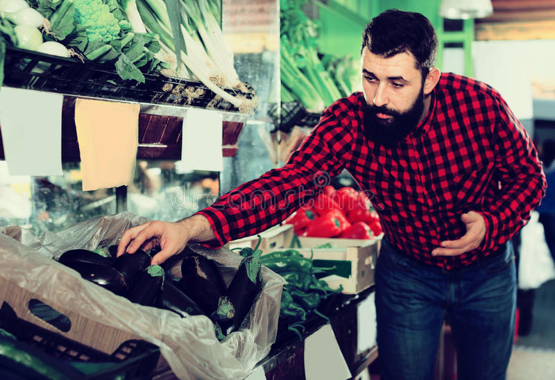 Man seller showing eggplants in grocery shop. Smiling man seller showing eggplants in grocery shop stock photo