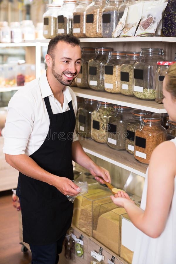Man seller standing with cereals sold. Man seller wearing apron standing with cereals sold by weight in organic shop royalty free stock image