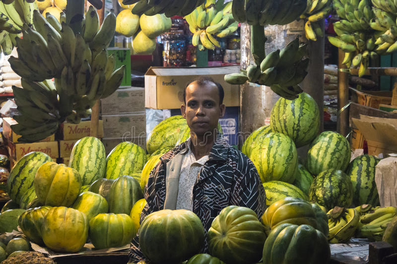 Man selling fruits in Chittagong, Bangladesh. CHITTAGONG, BANGLADESH - FEBRUARY 2017: Man with a small shop selling fruits in the central bazar market in royalty free stock photo