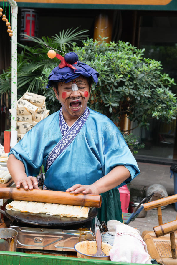 Man selling snack with show. Man selling snack at street dressed in opera costume,singing Chinese opera at chinese ancient town royalty free stock photography
