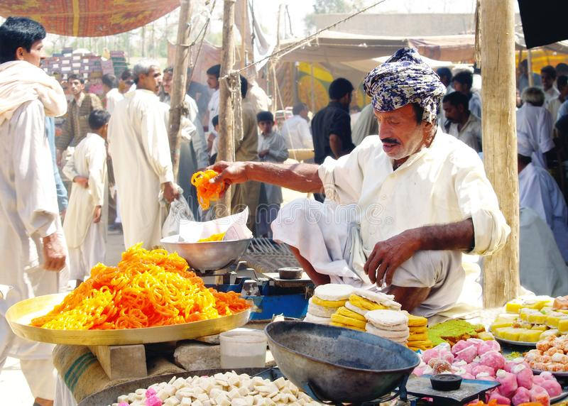 Man Selling Traditional Sweets. A happy villager man selling traditional sweets on a local market, in rural area of Pakistan. People in background are surfing in stock photo