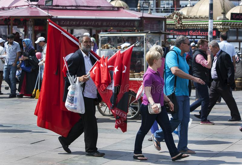 A man selling Turkish flags in Istanbul. A man selling Turkish flags walks along the pavement in the Eminonu district of Istanbul in Turkey stock photography