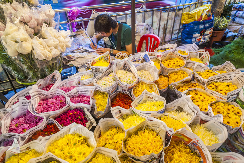 Man sells colorful flowers at the flowermarket in Bangkok early royalty free stock photo