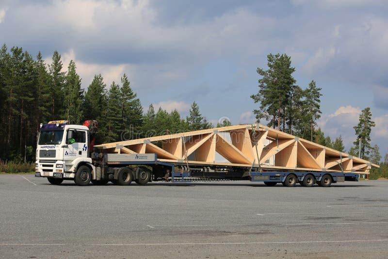 MAN Semi Truck Long Transport of Roof Truss. ORIVESI, FINLAND - SEPTEMBER 1, 2016: White MAN TGA 26.430 semi truck transports roof truss on flat trailer stock images