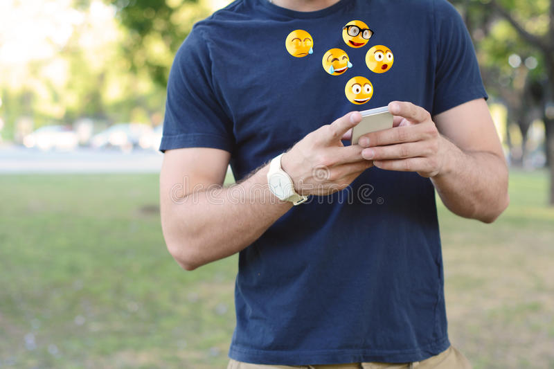 Man sending emoji emoticon. Portrait of young latin man typing on his phone with emoji emoticons. Emoji and communication concept. Outdoors stock image