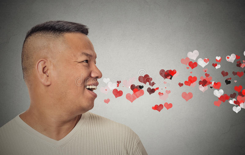 Man sending kisses, red hearts coming out of open mouth stock photography