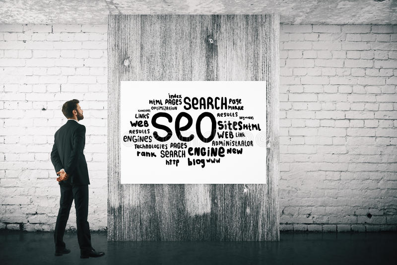 Man with SEO sketch. Back view of businessman in interior with SEO sketch on poster. 3D Rendering stock photos