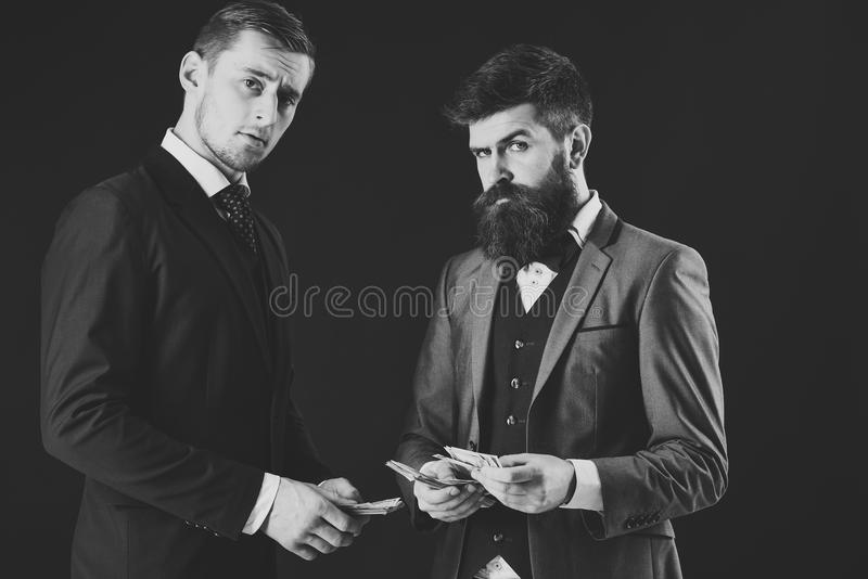 Man with serious emotion. Meeting of reputable businessmen, black background. Man with beard on serious face counting royalty free stock image