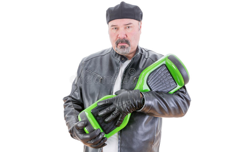 Man with serious expression with hoverboard. Rebellious middle aged man in leather jacket and gloves holding green and black hoverboard over white background royalty free stock photos