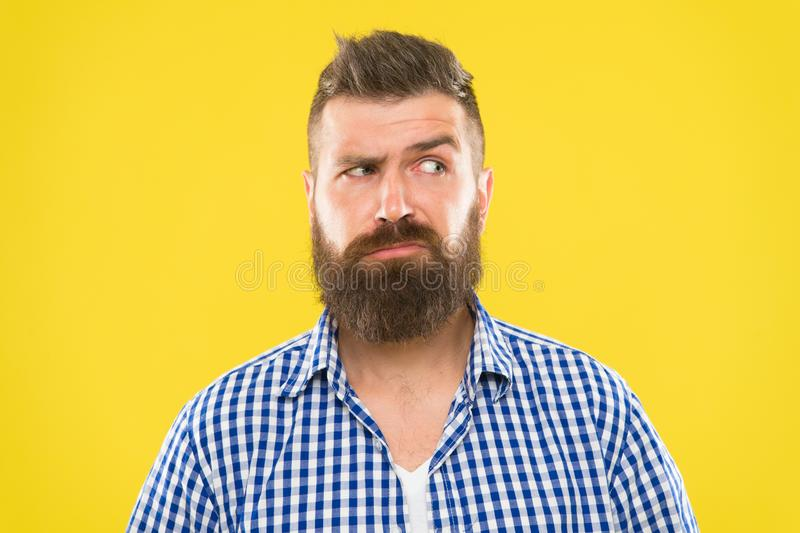 Man serious face raising eyebrow not confident. Have some doubts. Hipster bearded face not sure in something. Doubtful. Bearded man on yellow background close stock images