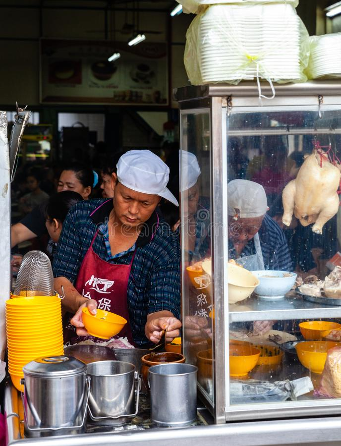 Man serves up chicken soup for clients on a food court of Ipoh royalty free stock photography