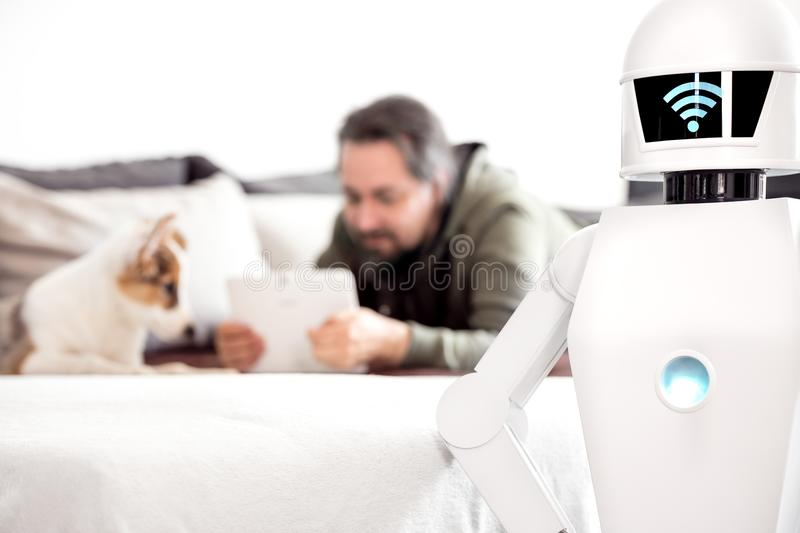 Man with service robot in the living room. Man is laying on a couch with his puppy dog and uses his tablet while his service household robot is standing in the stock images