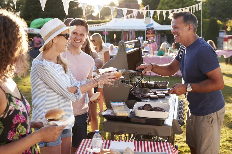 Man Serving On Barbeque Stall At Summer Garden Fete royalty free stock images