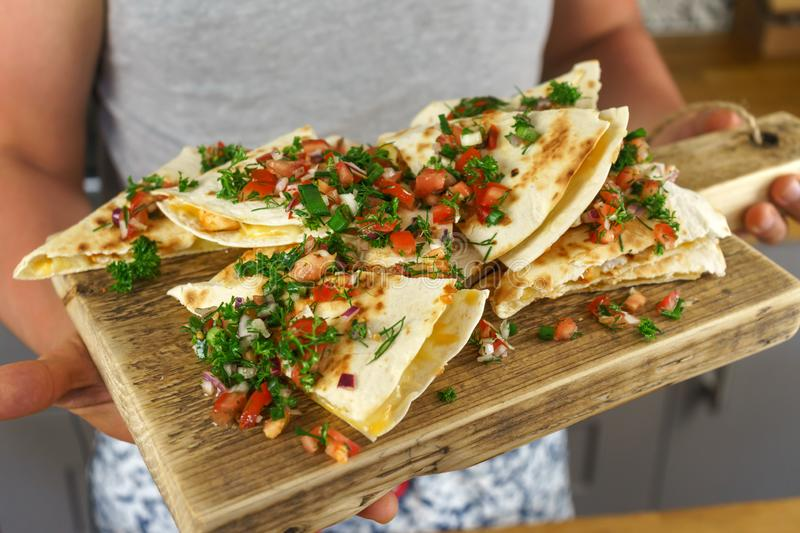 Man serving Mexican chicken quesadillas on wooden board royalty free stock photography