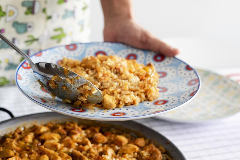 Man serving a spanish chicken paella. Closeup of a young caucasian man serving a plate of spanish chicken paella, from the paellera, the paella pan, freshly royalty free stock photo