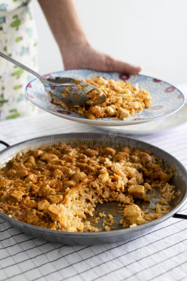 Man serving a spanish chicken paella. Closeup of a young caucasian man serving a plate of spanish chicken paella, from the paellera, the paella pan, freshly royalty free stock images