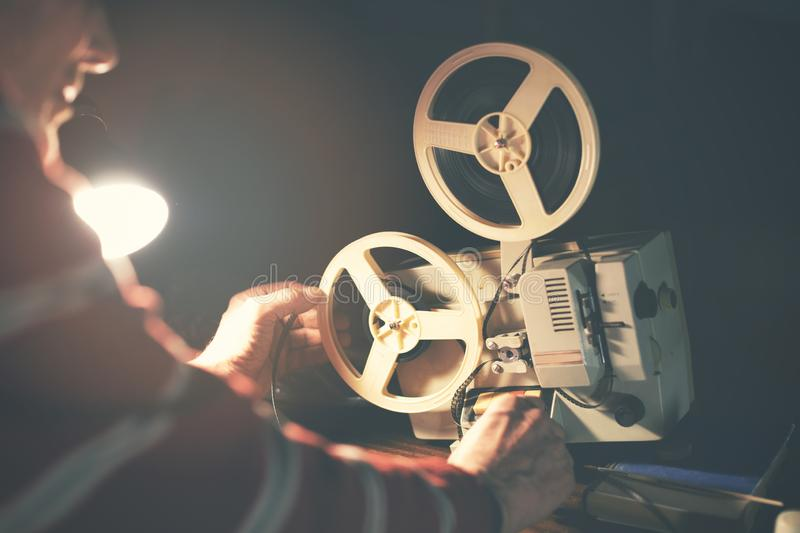 Man set up film reel on vintage 8mm movie projector stock photos