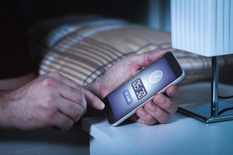 Man setting alarm to smartphone before going to sleep at night. Clock in mobile phone. Wake up early to work next morning royalty free stock images