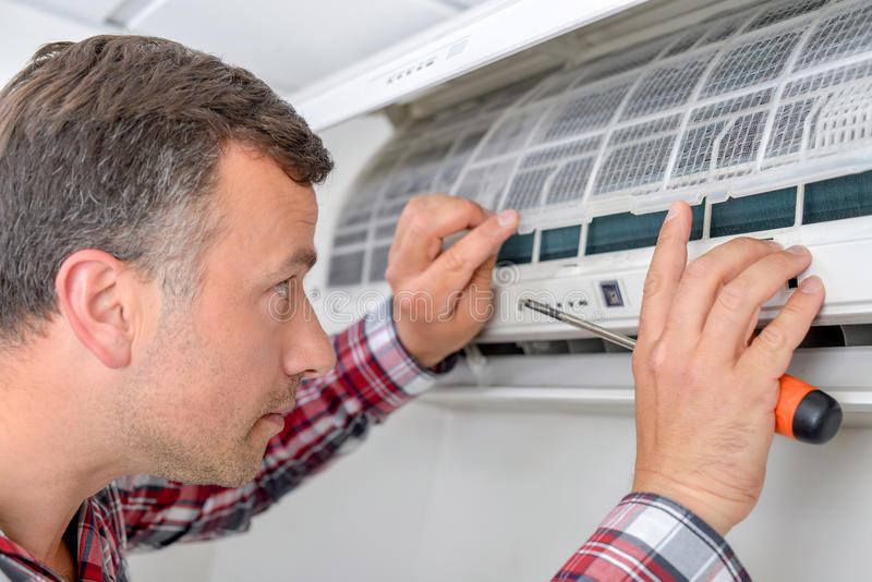 Man setting up an air conditioning unit. Man setting up air conditioning unit stock photos