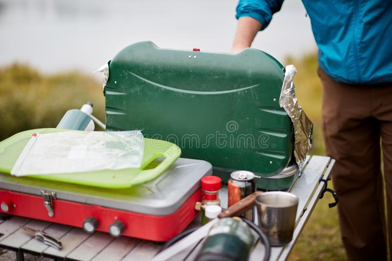 Man setting up a camping gas stove outdoors royalty free stock photography
