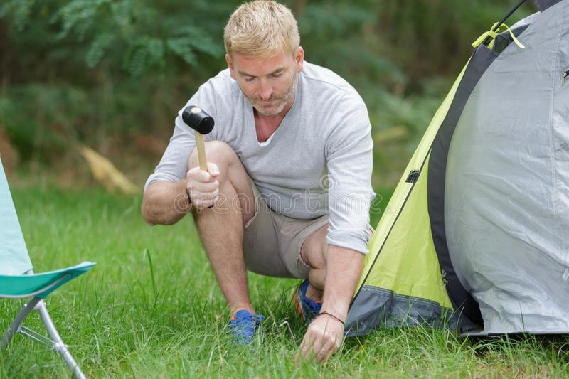 Man setting up tent at campsite. Man setting up the tent at campsite royalty free stock photography