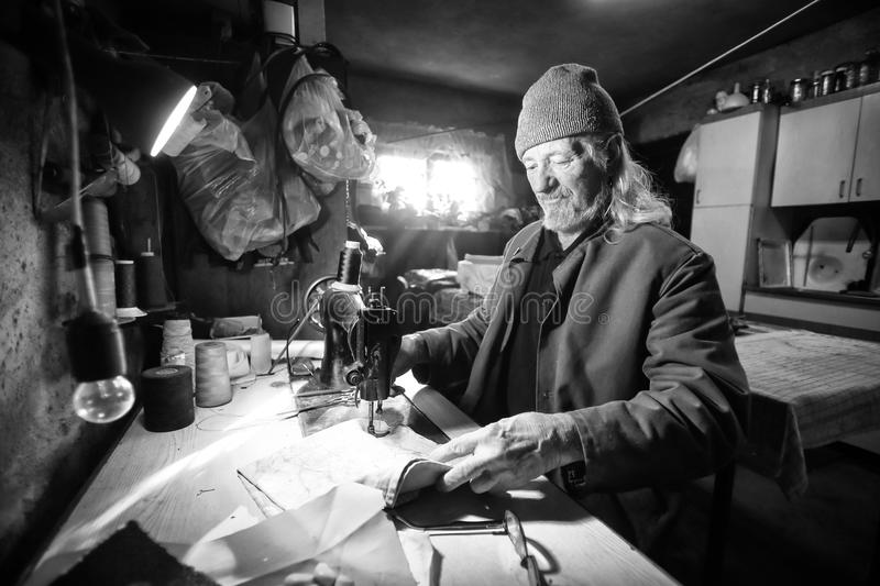 Man sewing fabric bw stock photography