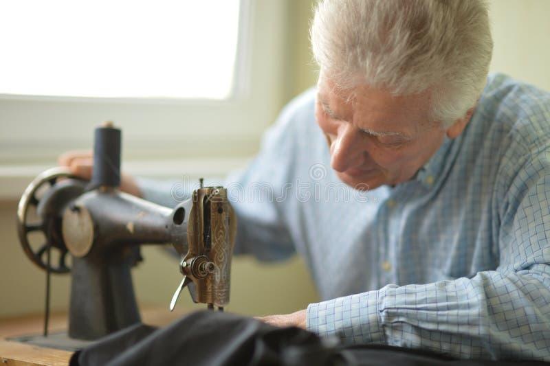 Man at sewing machine. Man working at sewing machine stock image
