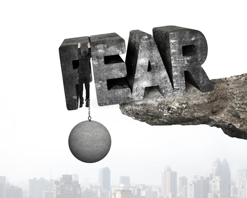 Man shackled by ball hanging fear word edge cliff cityscape. Man shackled by heavy concrete ball hanging on big 3D fear mottled word at the edge of cliff with royalty free stock images