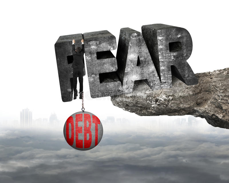 Man shackled debt ball hanging fear word edge cliff cloudscape. Man shackled by heavy red debt ball hanging on big 3D fear mottled concrete word at the edge of stock image