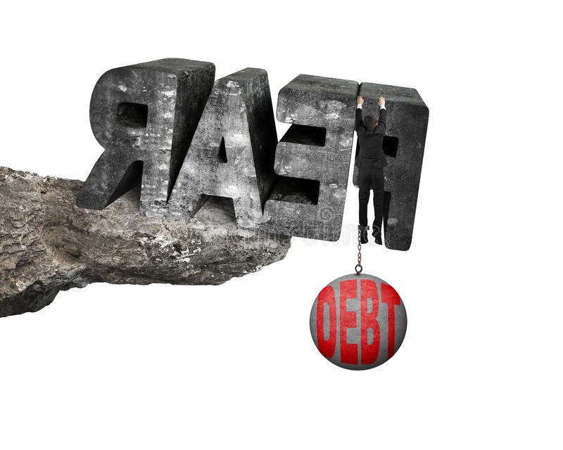 Man shackled by debt ball hanging fear word edge cliff. Man shackled by heavy red debt ball hanging on big 3D fear mottled concrete word at the edge of cliff stock photo