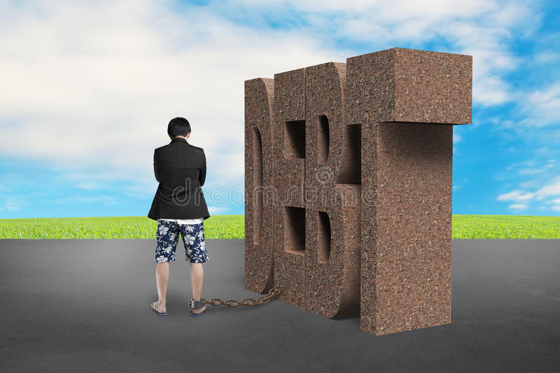 Man shackled by rusty DEBT. With sky stock photos
